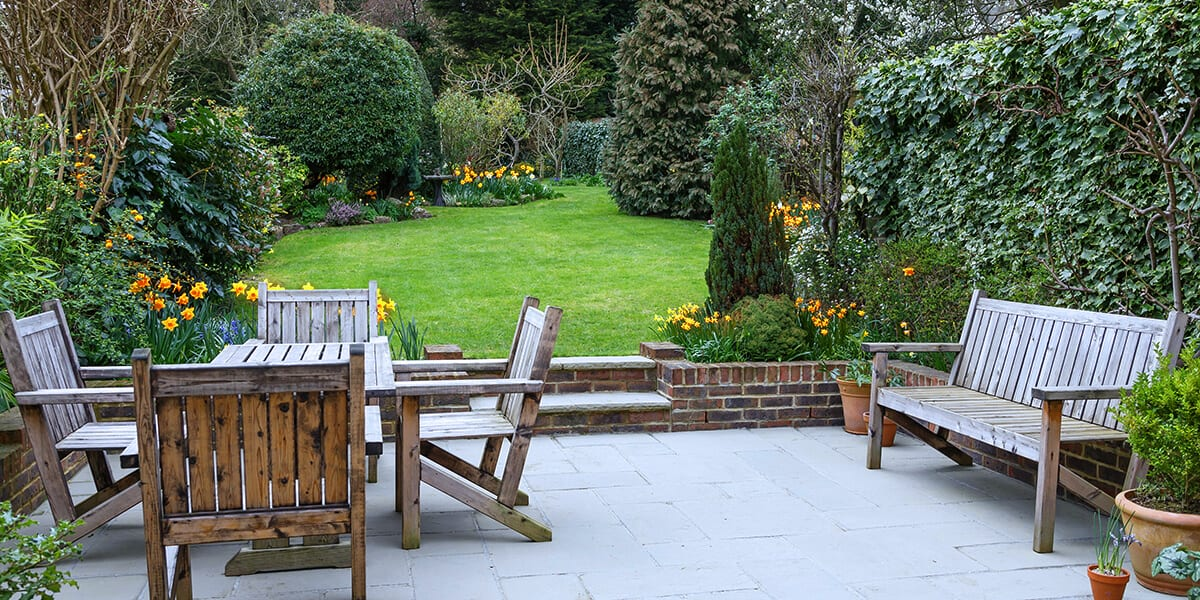 platt hill nursery fixes to common yard issues healthy garden with daffodils and patio furniture